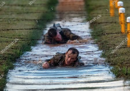 U.S. Army Capt. Michael Rose, of the 101th Airborne, crawls and under barbed wire strung across muddy water on the Melvesti course during the Best Ranger competition, at Fort Benning, Ga. Rose and his teammate Capt. John Bergman, background, won the event. Over 100 elite members of the U.S. military spent 60 grueling hours competing as two-member teams for the Best Ranger title