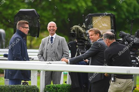 ITV presenter Ed Chamberlin second right gets mic'd up to the amusement of his colleagues during Horse Racing at Sandown Park Racecourse on 26th April 2019