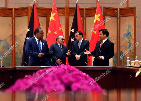 Chinese Premier Li Keqiang (2-R) with Papua New Guinea Prime Minister Peter O'Neill (2-L) attend a signing ceremony during their meeting at the Diaoyutai State Guesthouse in Beijing, China, 26 April 2019.
