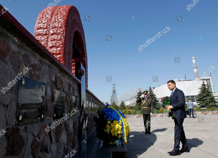 Ukrainian Prime Minister Volodymyr Groysman (R) lays flowers at the Monument for 'liquidators' who died during cleaning works after the Chernobyl nuclear power plant disaster at the monument wall in front of Chernobyl nuclear power plant, during a ceremony in Chernobyl, Ukraine, 26 April 2019. Ukrainians mark the 33rd anniversary of Chernobyl tragedy.  In the early hours of 26 April 1986 the Unit 4 reactor at the Chernobyl power station blew apart. Facing nuclear disaster on unprecedented scale Soviet authorities tried to contain the situation by sending thousands of ill-equipped men into a radioactive maelstrom. The explosion of Unit 4 of the Chernobyl nuclear power plant is still regarded the biggest accident in the history of nuclear power generation.