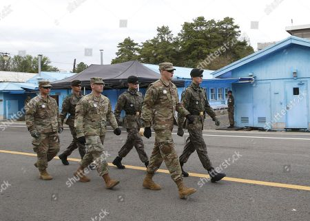 South Korean soldiers and US soldiers walk by a rehearsal for a Peace Performance to celebrate the First Anniversary of the Panmunjeom Declaration at the truce village of Panmunjom, Joint Security Area (JSA) of the Korean Demilitarized Zone (DMZ), 26 April 2019. The Panmunjom Declaration was adopted during the inter-Korean summit on 27 April 2018 aimed at cooperating on officially ending the Korean War and the Korean conflict, as well as includes the denuclearization of the Korean Peninsula.