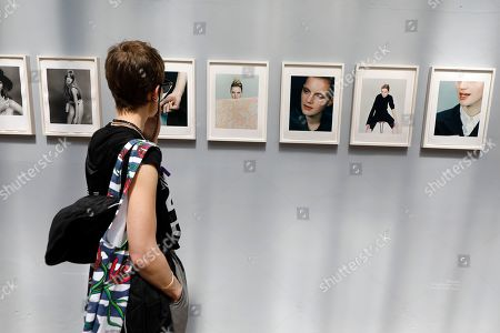 Stock Photo of A visitor looks at pictures on display in the exhibition 'One of One' by British photographer Craig McDean during the 34th International Festival of Fashion and Photography in Hyeres, southern France, 26 April 2019. The festival runs from 25 to 29 April.