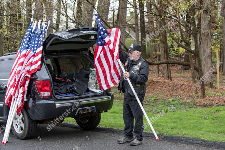 Cliff Fitzgerald, a member of the NY Riders and Patriot Guard unloads flags from his car to be held by people attending the funeral of Marine Private First Class Robert Graham on in Shrub Oak, NY. Graham, who died at 97 has no living family members but his friend Beth Regan arranged for hundreds to attend his funeral