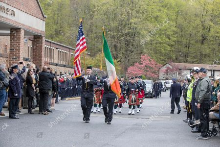 A hearse carrying the casket of Marine Private First Class Robert Graham is escorted by the Westchester Firefighters Emerald Society Pipes & Drums and New York City police officers on in Shrub Oak, NY. Graham has no living family members but his friend Beth Regan arranged for hundreds to attend his funeral