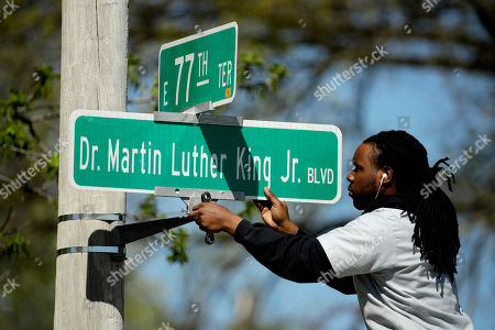 Stock Picture of April, 20, 2019, public works employee Jerry Brooks changes a street sign from the The Paseo to Dr. Martin Luther King, Jr. Blvd. in Kansas City, Mo. More than 50 years after King was assassinated, the city's efforts to honor the civil rights leader has met opposition from citizens opposed to the renaming of The Paseo, one of the city's iconic boulevards