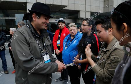 Duke Peltier, David Jackson. David Jackson, right, takes in the smoke from the burning sage held by First Nation Chief Duke Peltier during a cleansing ceremony outside the First Championship robotics competition, in Detroit. The First Nations STEM team that qualified for its first FIRST Championship is Ontario-based and is the only team made up of all indigenous students