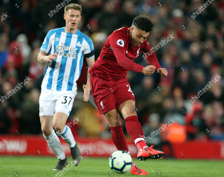 Huddersfield's Erik Durm, left, and Liverpool's Alex Oxlade-Chamberlain challenge for the ball during the English Premier League soccer match between Liverpool and Huddersfield Town at Anfield Stadium, in Liverpool, England