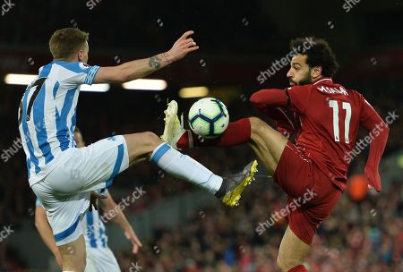 Liverpool's Mohamed Salah (R) vies for the ball against Huddersfield Erik Durm (L) during the English Premier League match between Liverpool FC and Huddersfield  at Anfield, Liverpool, Britain, 26 April 2019.