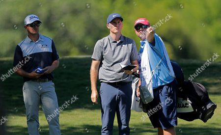Russell Henley, center, surveys a shot with his caddie as teammate Ryan Blaum, left, watches, on the 11th fairway during the second round of the PGA Zurich Classic golf tournament at TPC Louisiana in Avondale, La