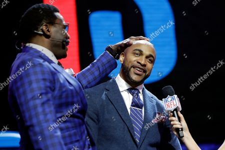 Former Dallas Cowboys player Michael Irvin, left speaks with former New York Giants player David Tyree during the third round of the NFL football draft, in Nashville, Tenn