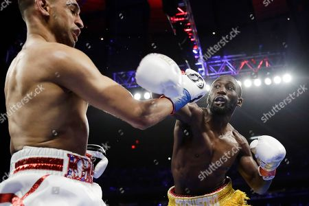 England's Amir Khan, left, evades a punch by Terence Crawford during the second round of a WBO world welterweight championship boxing match, in New York. Crawford won the fight