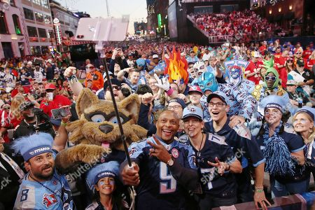 Former NFL player Eddie George takes a selfie with fans on the main stage during the second round of the NFL football draft, in Nashville, Tenn