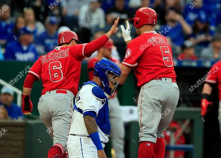 Stock Image of Los Angeles Angels' David Fletcher (6) high-fives teammate Albert Pujols (5) after his two-run home run during the first inning of a baseball game against the Kansas City Royals at Kauffman Stadium in Kansas City, Mo., . Kansas City Royals catcher Martin Maldonado, middle, waits for the next batter