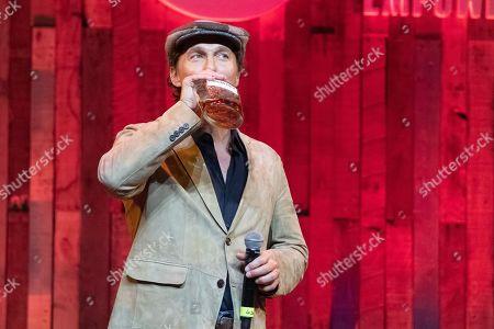 Matthew McConaughey drinks onstage
