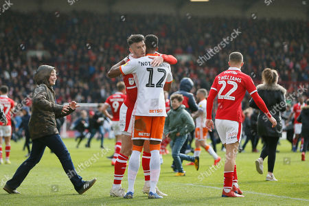 Blackpool defender Michael Nottingham (12) and Barnsley forward Kieffer Moore (19) embrace at full time as fans invade the pitch during the EFL Sky Bet League 1 match between Barnsley and Blackpool at Oakwell, Barnsley