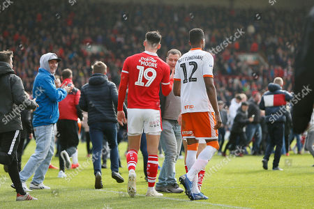 Blackpool defender Michael Nottingham (12) and Barnsley forward Kieffer Moore (19) at full time as fans invade the pitch during the EFL Sky Bet League 1 match between Barnsley and Blackpool at Oakwell, Barnsley