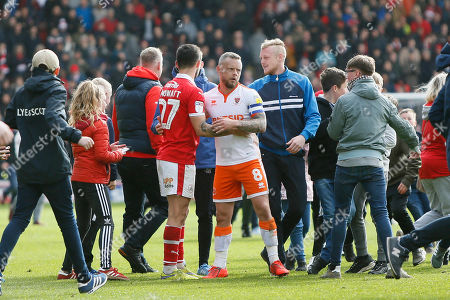Barnsley midfielder Alex Mowatt (27)  and Blackpool midfielder Jay Spearing (8)  embrace at full time as fans invade the pitch during the EFL Sky Bet League 1 match between Barnsley and Blackpool at Oakwell, Barnsley