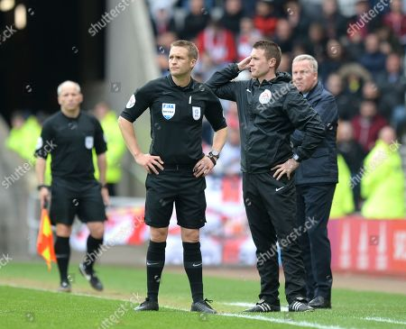 Referee Craig Pawson (centre) with fourth official Thomas Bramall wait for the flare that was thrown by Portsmouth fans to be removed before resuming play