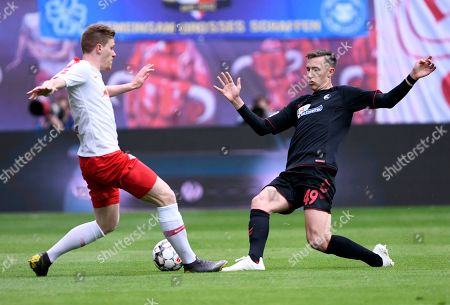 Leipzig's Marcel Halstenberg, left, challenges for the ball against Freiburg's Nico Schlotterbeck, right, during the German Bundesliga soccer match between RB Leipzig and SC Freiburg in Leipzig, Germany