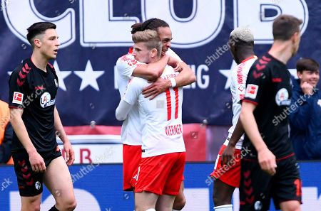 Leipzig's Timo Werner, 3rd left, celebrates after scoring the opening goal together with Leipzig's Yussuf Poulsen, 2nd left, during the German Bundesliga soccer match between RB Leipzig and SC Freiburg in Leipzig, Germany