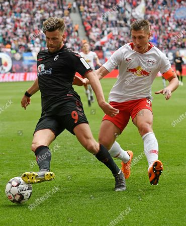 Leipzig's Willi Orban, right, challenges for the ball against Freiburg's Lucas Hoeler, left, during the German Bundesliga soccer match between RB Leipzig and SC Freiburg in Leipzig, Germany