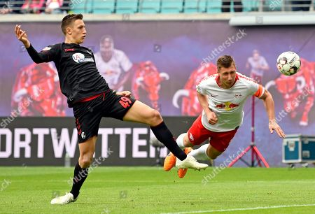 Leipzig's Willi Orban, right, challenges for the ball against Freiburg's Nico Schlotterbeck, left, during the German Bundesliga soccer match between RB Leipzig and SC Freiburg in Leipzig, Germany