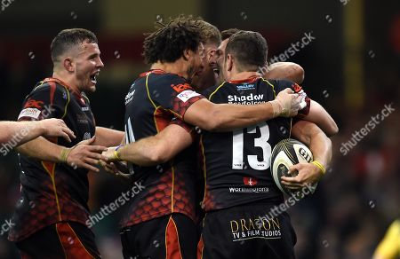 Josh Lewis of Dragons celebrates try with team mates.