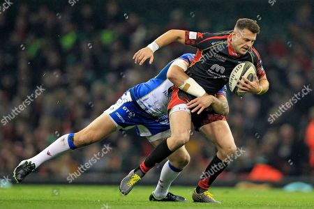 Stock Photo of Josh Lewis of Dragons is tackled by Hadleigh Parkes of Scarlets