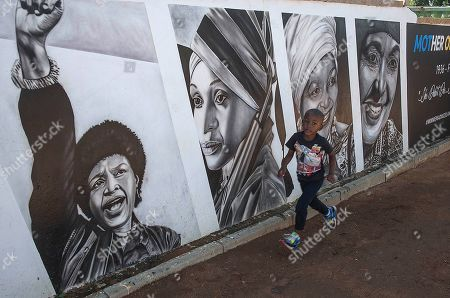 Stock Image of A boy passes a mural depicting the late Winnie Madikizela-Mandela in Soweto, South Africa as the country celebrates Freedom Day. The country celebrates the day which commemorates the 25th anniversary of the end of apartheid