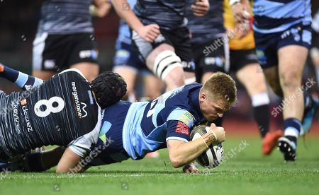 Gareth Anscombe of Cardiff Blues beats tackle by James King of Ospreys to score try.
