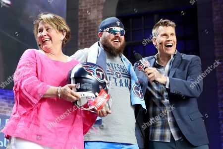 Tennessee Titans controlling owner Amy Adams Strunk is seen with NFL RedZone host Scott Hanson and a Titans fan who was gifted an autographed helmet on Day 3 of the NFL football draft, in Nashville, Tenn. on