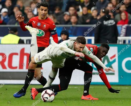 Rennes' Benjamin Andre, left, looks on as Rennes' Ismaila Sarr, right, challenges PSG's Julian Drexler, center, during the French Cup soccer final between Rennes and Paris Saint Germain at the Stade de France stadium in Saint-Denis, outside Paris, France
