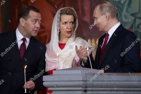Patriarch Kirill, Vladimir Putin, Dmitry Medvedev, Svetlana Medvedeva. Russian President Vladimir Putin, right, Prime Minister Dmitry Medvedev, left, and Medvedev's wife Svetlana talk to each other as they attend the Easter service in the Christ the Savior Cathedral in Moscow, Russia, . Orthodox Christians around the world celebrate Easter on Sunday, April 28