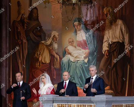 Patriarch Kirill, Vladimir Putin, Dmitry Medvedev, Svetlana Medvedeva, Sergei Sobyanin. Russian President Vladimir Putin, right, Prime Minister Dmitry Medvedev, left, Medvedev's wife Svetlana, and Moscow's Mayor Sergei Sobyanin, right, cross themselves during the Easter service in the Christ the Savior Cathedral in Moscow, Russia, . Orthodox Christians around the world celebrate Easter on Sunday, April 28