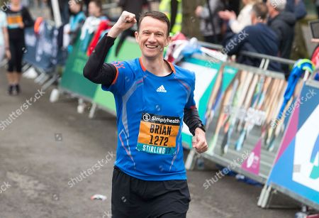 Stock Picture of Brian Welsh crosses the line of the Simplyheath Great Stirling Run