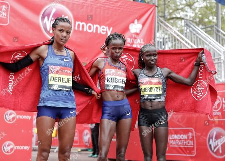 First place winner Kenya's Brigid Kosgei, center poses with second place winner Kenya's Vivian Cheruiyot, right, and third place winner Ethipoia's Roza Dereje after the women's race at the 39th London Marathon in London