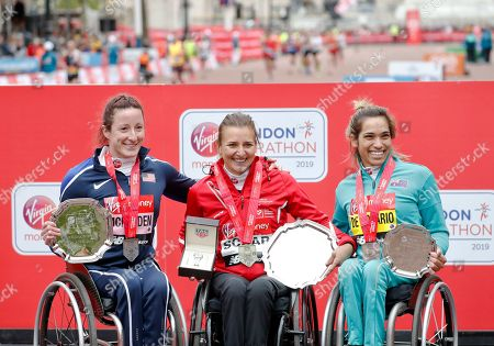 Women's wheelchair race first place winner Switzerland's Manuela Schar, center, poses with second place winner Tatyana McFadden of the United States, left, and third place winner Australia's Madison de Rozario at the 39th London Marathon in London
