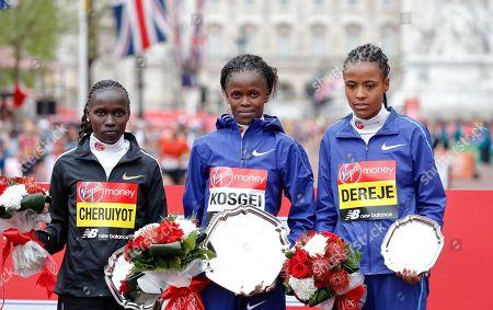 Women's race first place winner Kenya's Brigid Kosgei, center, poses with second place winner Kenya's Vivian Cheruiyot, left, and third place winner Ethipoia's Roza Dereje at the 39th London Marathon in London