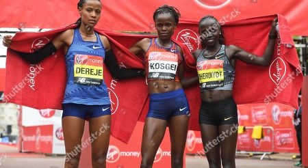 Stock Image of Third placed, Ethiopia's Roza Dereje (L), winner, Kenya's Brigid Kosgei (C) and second placed, Kenya's Vivian Cheruiyot (R)  pose after crossing the finishing line during the 2019 Virgin Money London Marathon in London, Britain, 28 April 2019.