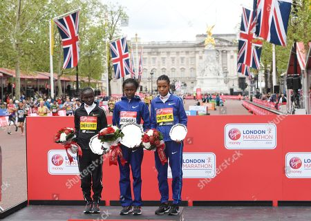 Second placed, Kenya's Vivian Cheruiyot (L), winner, Kenya's Brigid Kosgei (C) and third placed, Ethiopia's Roza Dereje (R) pose at the medal ceremony for the elite women's race during the 2019 Virgin Money London Marathon in London, Britain, 28 April 2019.