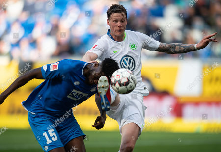 Wout Weghorst of Wolfsburg (R) in action with Kasim Adams of Hoffenheim during the German Bundesliga soccer match between TSG 1899 Hoffenheim and VfL Wolfsburg in Sinsheim, Germany, 28 April 2019.