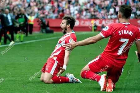 Girona's Cristian Portugues 'Portu' (L) celebrates with Uruguayan Cristhian Stuani (R) after scoring the opening goal against Sevilla FC during their Spanish LaLiga Primera Division soccer match played at the Montillivi stadium in Gerona, Spain, 28 April 2019.