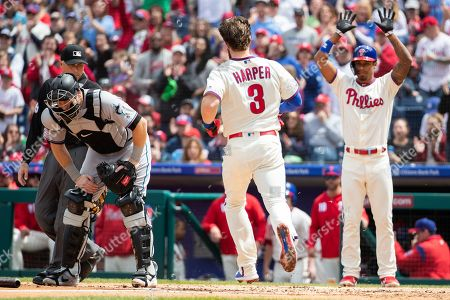 Philadelphia Phillies' Bryce Harper (3) comes in to score as Miami Marlins catcher Chad Wallach (17) looks down during the MLB game between the Miami Marlins and Philadelphia Phillies at Citizens Bank Park in Philadelphia, Pennsylvania