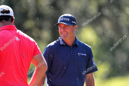Ryan Palmer talks with teammate Jon Rham on the 15th green during the final round of the PGA Zurich Classic golf tournament at TPC Louisiana in Avondale, La
