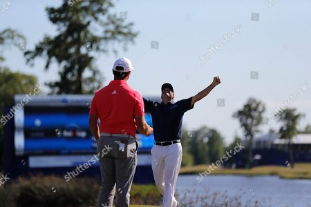 Ryan Palmer throws his arms in the air as he celebrates with teammate Jon Rahm as they win the PGA Zurich Classic golf tournament at TPC Louisiana in Avondale, La