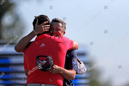 Ryan Palmer, facing, hugs teammate Jon Rahm as they win the PGA Zurich Classic golf tournament at TPC Louisiana in Avondale, La