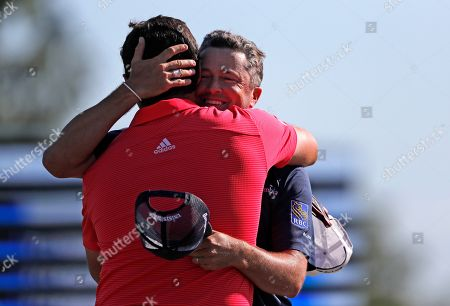 Ryan Palmer, right, hugs teammate Jon Rahm as they win the PGA Zurich Classic golf tournament at TPC Louisiana in Avondale, La