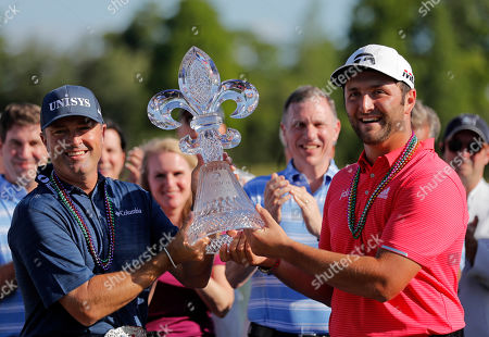 Ryan Palmer, left, and Joh Rahm hold their tournament trophy after winning the PGA Zurich Classic golf tournament at TPC Louisiana in Avondale, La