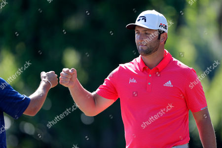 Jon Rahm, right, celebrates with teammate Ryan Palmer offer squeaking out a par on the 15th green during the final round of the PGA Zurich Classic golf tournament at TPC Louisiana in Avondale, La