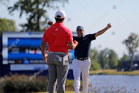 Ryan Palmer, right, celebrates with teammate Jon Rahm as they win the PGA Zurich Classic golf tournament at TPC Louisiana in Avondale, La